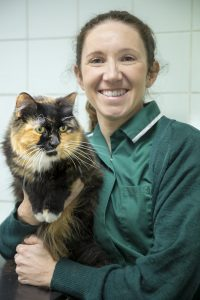 Veterinary Nurse Looking Happy While Holding Black and Ginger Cat