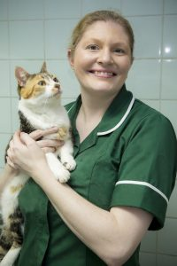 Veterinary Nurse Smiling While Holding Small Cat