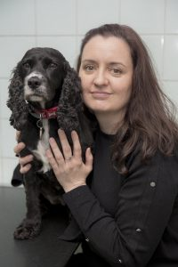 Palmerston Staff Member Holding Black Dog While Smiling